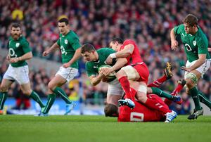 Brian O'Driscoll is tackled by Rhys Priestland and Jamie Roberts as Ireland powered to victory over wales at the Aviva Stadium