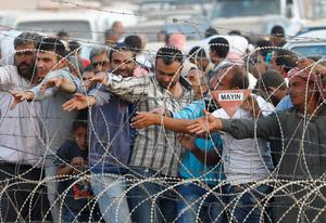 Syrian Kurdish men try to get water which is distributed by Turkish Red Crescent as they wait behind the border fences to cross into Turkey
