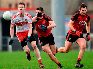 Oisin Duffin of Derry in action against Ryan McAleenan of Down. Photo: Sportsfile