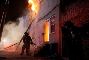 Baltimore firefighters fight a fire inside a burning building set ablaze by rioters on East Biddle street during clashes after the funeral of Freddie Gray in Baltimore, Maryland in the early morning hours of April 28, 2015. REUTERS/Jim Bourg