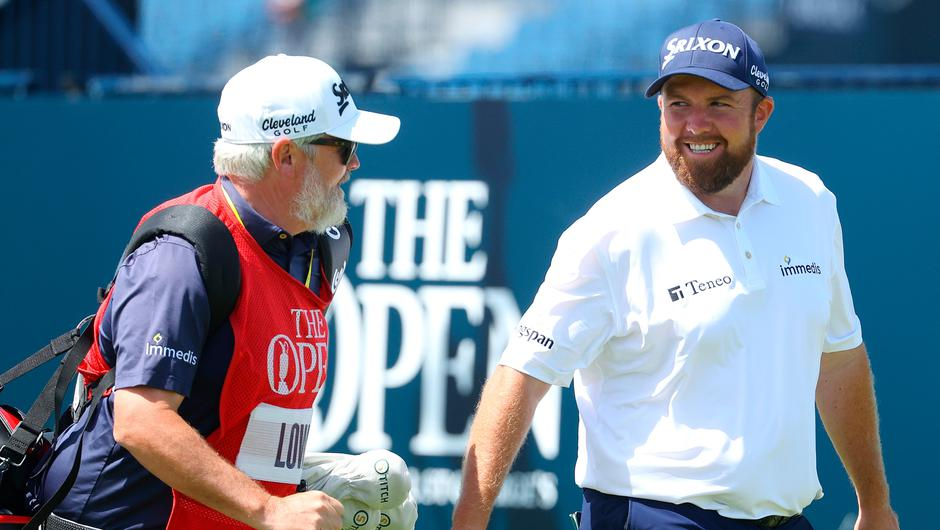 Shane Lowry of Ireland talks to his caddie, Brian 'Bo' Martin during Day Three of The 149th Open at Royal St Georges Golf Club