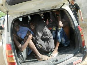 Students of the Garissa University College take shelter in a vehicle after fleeing from an attack by gunmen in Garissa, Kenya (AP Photo)