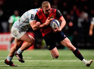 Munster's Keith Earls is challenged by Racing's Camille Chat. Photo: Getty Images