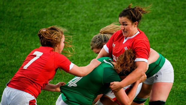 Aoife McDermott of Ireland is tackled by Manon Johnes, left, and Siwan Lillicrap of Wales. Photo: Ramsey Cardy/Sportsfile