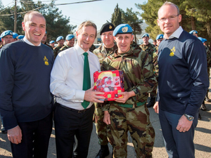 Taoiseach Enda Kenny - pictured with Junior Defence Minister Paul Kehoe (left), Chief of Staff Vice Admiral Mark Mellett (rear) and Defence Minister Simon Coveney (right) – gives Pte David O'Meara a present from his father, Coy Sgt Paul O'Meara, who is serving in Southern Lebanon Photo: Mark Condren