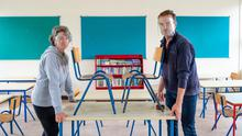 Bigger classes: The loss of a teacher at St Patrick's NS in Harestown, Co Louth, means that pupils from senior infants to third class will be taught in groups of mixed levels. Principal Fiachra Bell and school secretary Mary McCabe rearrange furniture to safely accommodate the pupils. Photo: Ciara Wilkinson