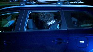 A man detained by police during a raid sits in a car in Sydney, in this still image taken from police handout video September 18, 2014. REUTERS/Australian Federal Police/Handout via Reuters