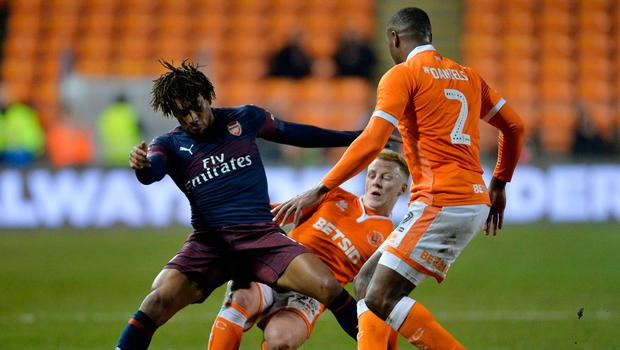 Arsenal's Alex Iwobi in action with Blackpool's Chris Taylor and Donervon Daniels. Photo: Peter Powell/Reuters