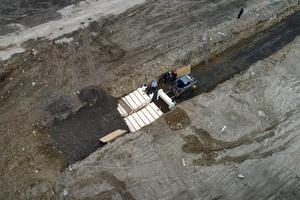Workers wearing personal protective equipment bury bodies in a trench on Hart Island  (AP Photo/John Minchillo)