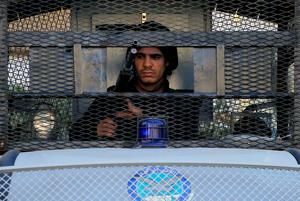 A policeman stands guard behind an armoured vehicle at Talaat Harb Square in Cairo. Reuters