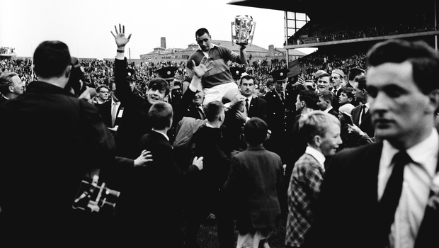 Jimmy Doyle holds the Liam MacCarthy Cup as he is held aloft by Tipperary supporters after his side's vitory over Wexford in 1965