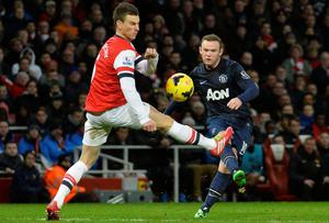 Manchester United's Wayne Rooney (R) is challenged by Arsenal's Laurent Koscielny d