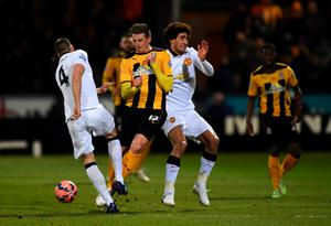 Liam Hughes of Cambridge United battles for the ball with Marouane Fellaini and Phil Jones of Manchester United during the FA Cup Fourth Round