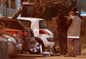 Police investigators search for evidence as an unidentified man is detained (L) during an operation in the eastern French city of Reims January 8, 2015, after the shooting against the Paris offices of Charlie Hebdo, a satirical newspaper. REUTERS/Christian Hartmann