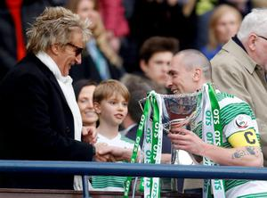 Rod Stewart (left) presents Celtic's Scott Brown with the cup after Celtic won the QTS Scottish League Cup Final at Hampden Park