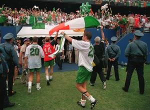 Jason McAteer holds the flag of Ireland aloft and salutes the crowd after Ireland drew 0-0 with Norway to qualify for the next phase of the 1994 World Cup after their match at Giants Stadium in East Rutherford, New Jersey. Photo: Getty Images
