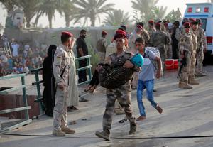An Iraqi soldier carries a displaced girl to help her cross the bridge at the outskirts of Baghdad, May 19, 2015. REUTERS/Stringer