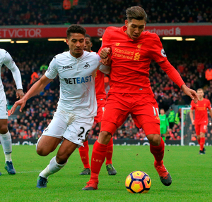 Swansea City's Kyle Naughton (left) and Liverpool's Roberto Firmino battle for the ball during the Premier League match at Anfield. Photo: Peter Byrne/PA