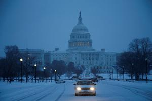 A police car sits at the entrance to a parking lot in the snow at the U.S. Capitol in Washington, February 13, 2014.   REUTERS/Jonathan Ernst    (UNITED STATES - Tags: POLITICS ENVIRONMENT)