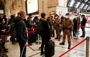 Police officers and soldiers check passengers leaving from Milan main train station, Italy, Monday, March 9, 2020. Areas under lockdown include Milan, Italy's financial hub and the main city in Lombardy, and Venice, the main city in the neighboring Veneto region. (AP Photo/Antonio Calanni)