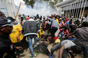 Residents desperate for a planned distribution of food for those suffering under Kenya's coronavirus-related movement restrictions push through a gate and create a stampede, causing police to fire tear gas. Photo: Khalil Senosi/AP Photo