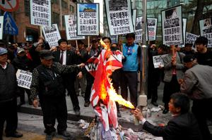 """A South Korean conservative right-wing protester burns a Japanese """"rising sun"""" flag as they chant slogans during an anti-Japan rally in front of the Japanese embassy in Seoul"""