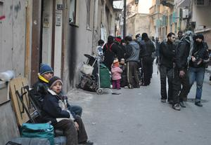 Syrians gather with their belongings in a street of a besieged district of the central city of Homs on February 8, 2014 as a United Nations and Syria's Red Crescent humanitarian convoy (unseen) delivers food and medical aid.