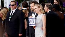 """Actors Joshua Jackson and Diane Kruger hold a """"Je Suis Charlie"""" sign on the red carpet at the 72nd Golden Globe Awards in Beverly Hills, California January 11, 2015.  REUTERS/Mario Anzuoni  (UNITED STATES - Tags: ENTERTAINMENT)(GOLDENGLOBES-ARRIVALS)"""