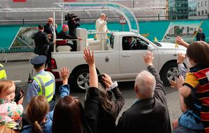 Pope Francis waves to the waiting crowds as he travels in the Popemobile through Dublin during his visit to Ireland. Photo: Brian Lawless/PA Wire