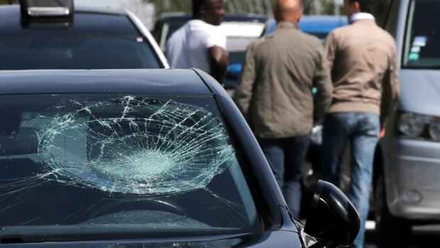 A damaged car is parked on the motorway near Orly airport as striking taxi drivers block access roads south of Paris, France, during a national protest against car-sharing service Uber June 25, 2015. French taxi drivers stepped up protests against U.S. online cab service UberPOP on Thursday, blocking road access to airports and train stations in Paris and other cities. REUTERS/Christian Hartmann