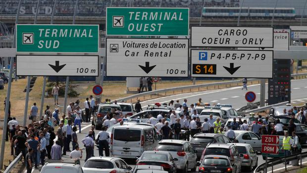 French striking taxi drivers block the access to Orly airport, south of Paris, France, during a national protest against car-sharing service Uber June 25, 2015. French taxi drivers stepped up protests against U.S. online cab service UberPOP on Thursday, blocking road access to airports and train stations in Paris and other cities. REUTERS/Christian Hartmann  ATTENTION EDITORS : FRENCH LAW REQUIRES THAT REGISTRATION PLATE CAN NOT BE PUBLISHED IN FRANCE