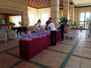 Employees wearing protective masks arrange water bottles in the lobby of a hotel under lockdown after a coronavirus case was identified in Adeje, in the Spanish Canary Island of Tenerife, Spain, February 25, 2020. Christopher Betts via REUTERS