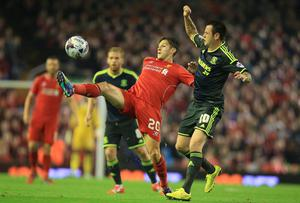Liverpool midfielder Adam Lallana controls the ball as Middlesbrough's Lee Tomlin looks on during the Capital One Cup clash at Anfield. Photo: Peter Byrne/PA Wire