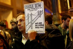 Regis Danon, of France, holds a drawing as he takes part in a vigil outside the Consulate General of France to pay tribute to the victims of the suspected Islamist attack on satirical magazine Charlie Hebdo in Paris, in San Francisco, California January 7, 2015. REUTERS/Stephen Lam