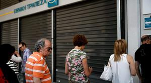 People line up at an ATM outside a National Bank branch in Athens, Greece June 29, 2015. Greeks woke up to shuttered banks, closed cash machines and a climate of rumours and conspiracy theories on Monday as a breakdown in talks between Athens and its creditors plunged the country deep into crisis