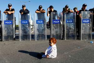 An infant sits on the road in front of a line of Turkish police who block migrants on a highway near Edirne, Turkey yesterday
