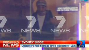 This image taken from video shows a man believed to be a gunman inside a cafe in Sydney, Australia. (AP Photo/Channel 7 via AP Video)