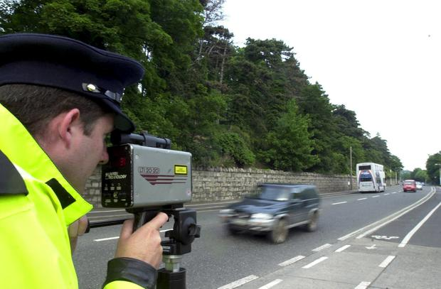 GARDAI SPEEDING CARS CAMERAS ROAD SAFETY DANGEROUS DRIVING CHECKPOINTS...Garda James Walsh look through a speed camera on Dublin`s Chapelizod Rd as part of operation Taisteal a national safety campaign over the June Bank Holiday Weekend. 30/5/2003
