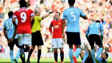 Wayne Rooney of Manchester United receives a red card from referee Lee Mason after a foul on Stewart Downing of West Ham