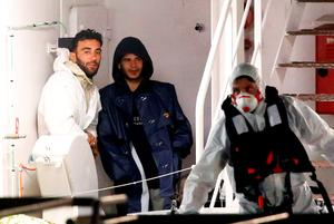 Mohammed Ali Malek (L) and Mahmud Bikhit (C), two survivors of Saturday's migrant boat disaster, arrested on suspicion of people trafficking, are seen as they arrive by Italian coastguard ship Bruno Gregoretti in Catania's harbour. Photo: Reuters