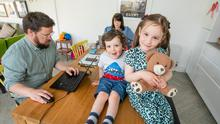 BUSY DAYS: Paul Sheridan and Sara Bermingham working from the kitchen table with their children Annie and David. Photo: Mark Condren