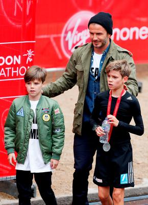 Romeo Beckham (R) receives the support of his brother Cruz Beckham (L) and father David Beckham (C) after taking part in the junior marathon During the Virgin Money London Marathon on April 26, 2015 in London, England.  (Photo by Steve Bardens/Getty Images)