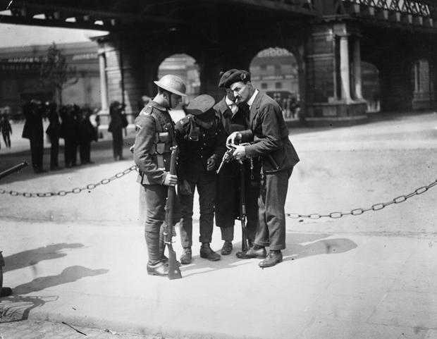 History: British soldiers watch a member of the Black and Tans reload his .45 revolver after the burning of the Custom House in Dublin in 1921. Photo: Walshe/Getty Images