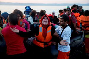 A woman reacts as she arrives aboard a dinghy after crossing from Turkey, to the island of Lesbos, Greece, on Saturday, Sept. 19, 2015.  (AP Photo/Petros Giannakouris)