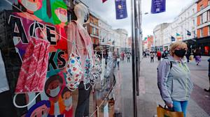 A woman walks past a shop selling masks on Dublin's Grafton Street. Photo: Niall Carson/PA Wire