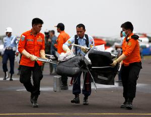 Parts of AirAsia QZ8501, recovered from the Java Sea, are carried by Indonesian Airforce and Search and Rescue crew after they were offloaded from a US Navy helicopter at the airport. REUTERS/Darren Whiteside