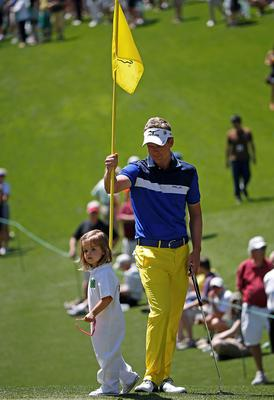 Britain's Luke Donald stands with his daughter Ellie on the first hole of the annual Par 3 contest. Photo: Reuters