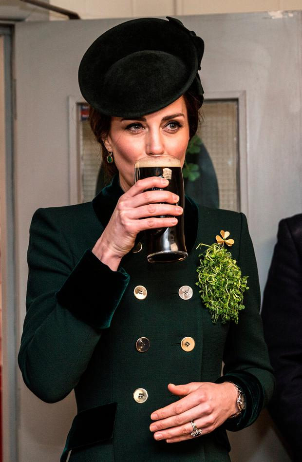 The Duchess of Cambridge takes a drink of Guinness as she meets with soldiers of the 1st Battalion Irish Guards following their St Patrick's Day parade at Cavalry Barracks, Hounslow (REUTERS/Richard Pohle)
