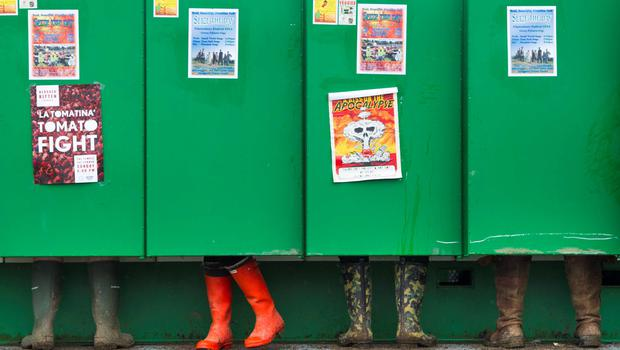 Festivalgoers using the newly installed long drop toilets in the rain at the Glastonbury Festival. PA