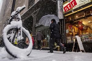 People walk through the snow during the morning commute in New York's financial district near Wall Street